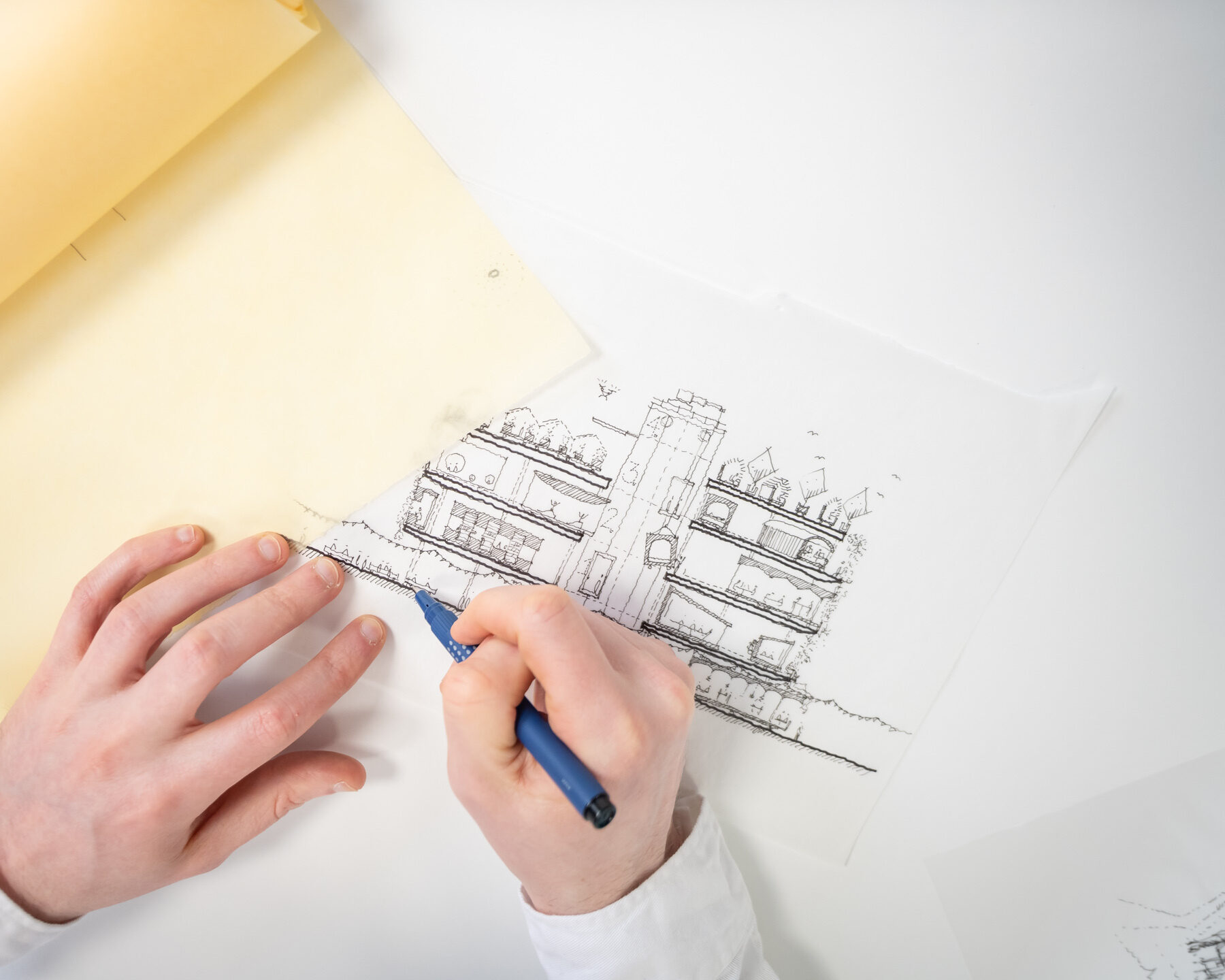 Hands sketching a sustainable building model